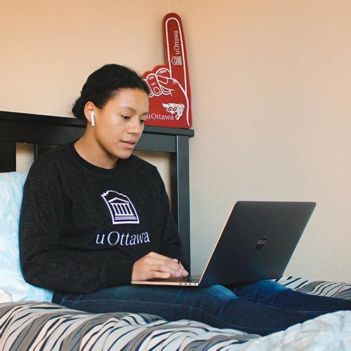 Une fille assise dans son lit sur son ordinateur portable