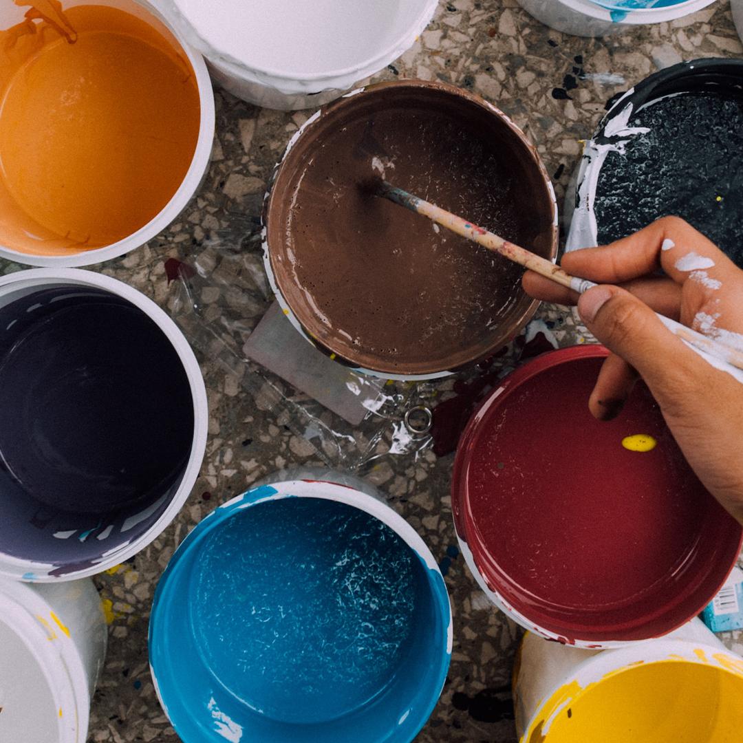 Un pinceau est trempé dans un pot de peinture. Plusieurs autres pots de peinture se trouvent autour.