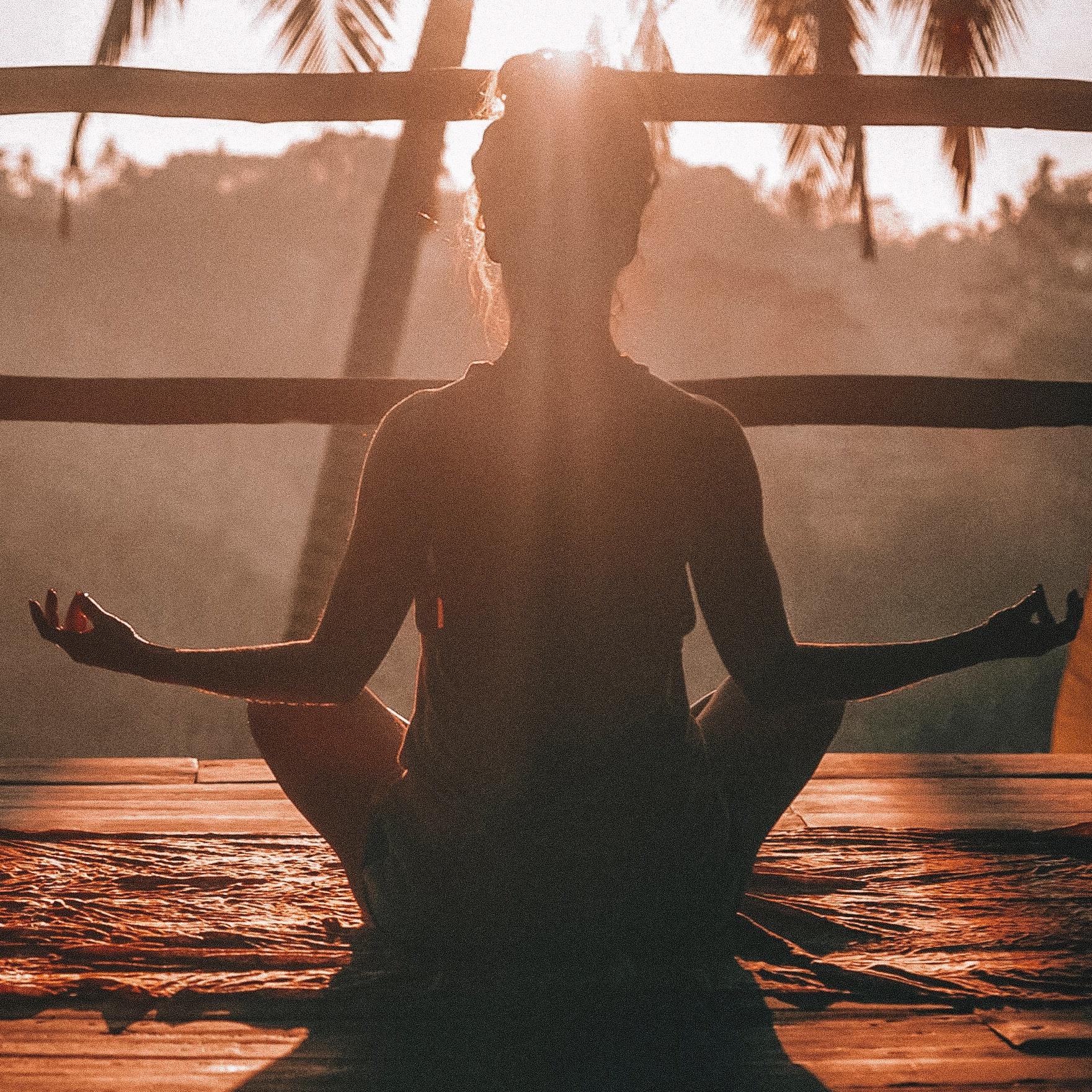 femme en train de méditer au coucher du soleil
