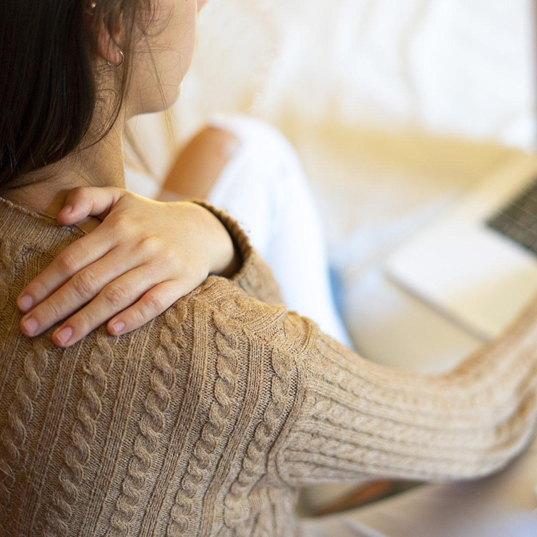 Une femme assise avec sa main sur son épaule
