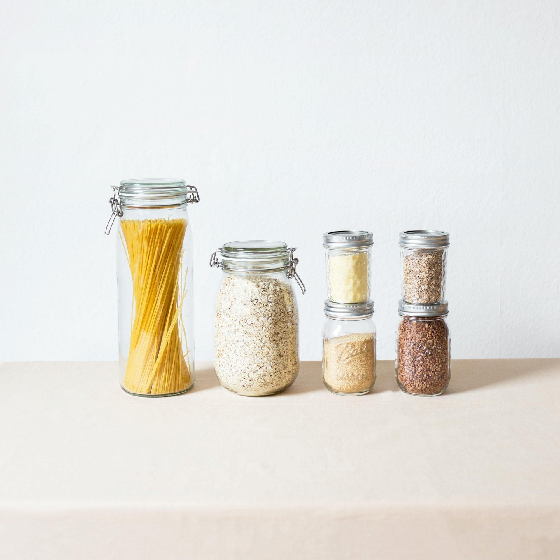 Des bocaux de maçon remplis de pâtes, de graines et d'herbes.