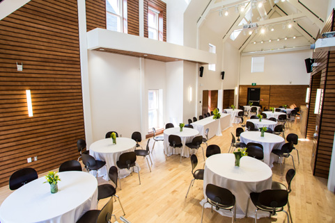 View of the Johnston room in the Alex Trebek Alumni Hall with a set up of tables with white tablecloths and empty chairs.
