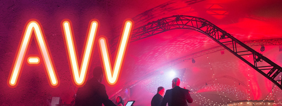 Alumni Week logo with the an A and W in neon and two people in the background