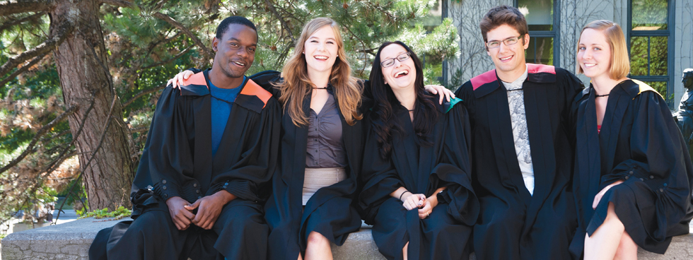 Five University of Ottawa graduates smiling and laughing while standing in front of Tabaret Hall stairs.