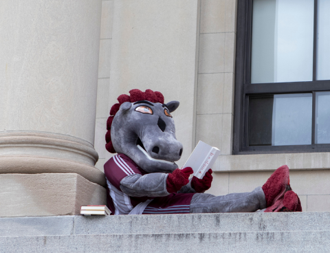 GeeGees mascot sitting comfortably at Tabaret hall reading a book
