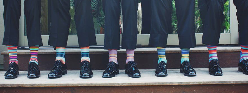 Men lifting the bottom of their pants to show colourful socks