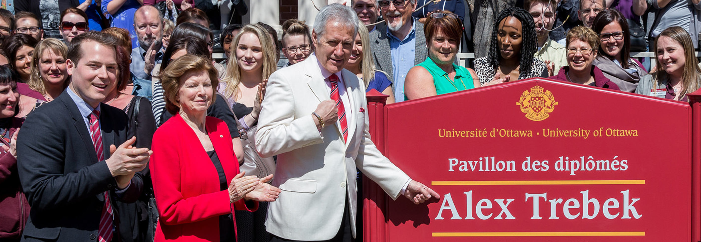 Alex Trebek standing in front of the new Alex Trebek Hall sign with people around him celebrating