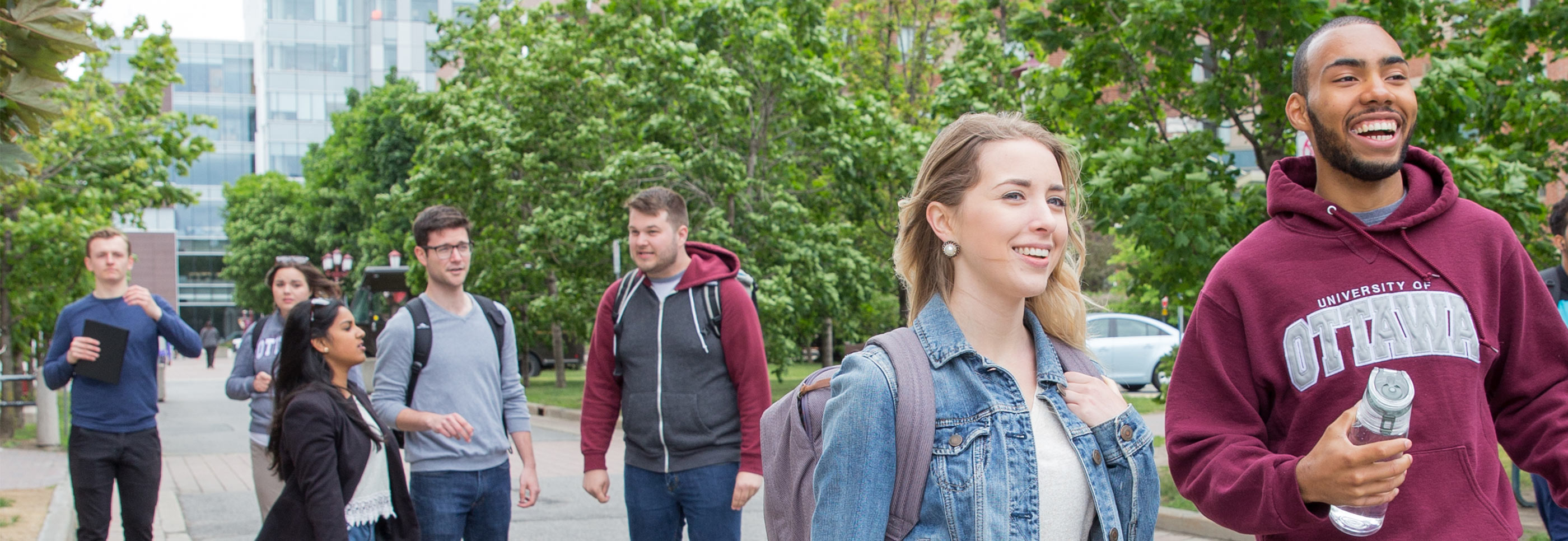 Seven students walking in the main pedestrian alley, smiling with FSS in the background