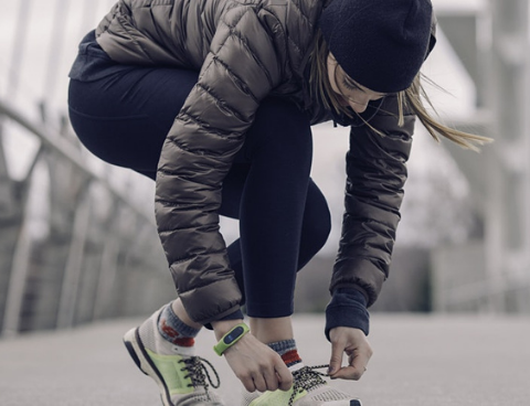 Woman tying her running shoe and getting ready to run or walk in the crisp fall air