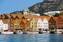 Norway village with colourful houses, boats on the water and mountains in background.