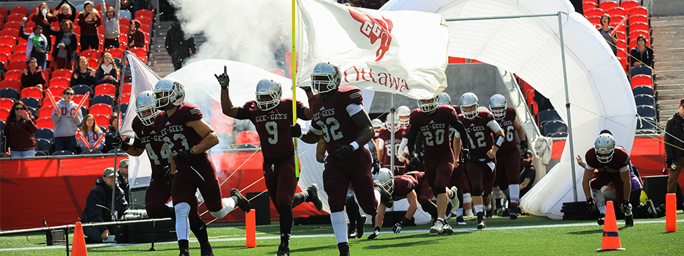 Gee Gees football team coming out onto the field with the uOttawa flag