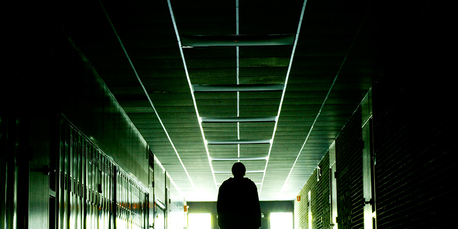 Lockdown: Ominous shadowy figure walking down a hallway lined with lockers.