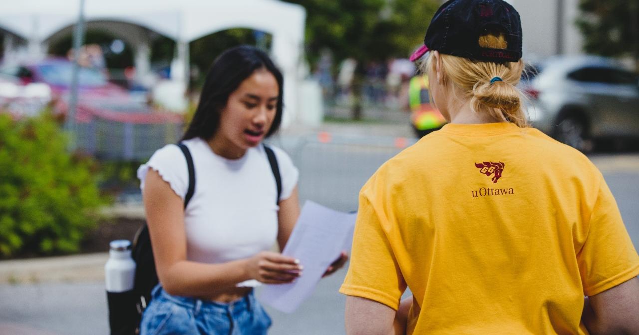 Une jeune femme tenant du papier demandant à une autre personne portant une chemise jaune pour les directions