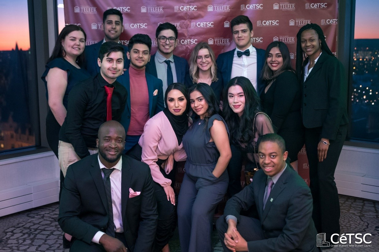Group of students in front of a backdrop at an event.