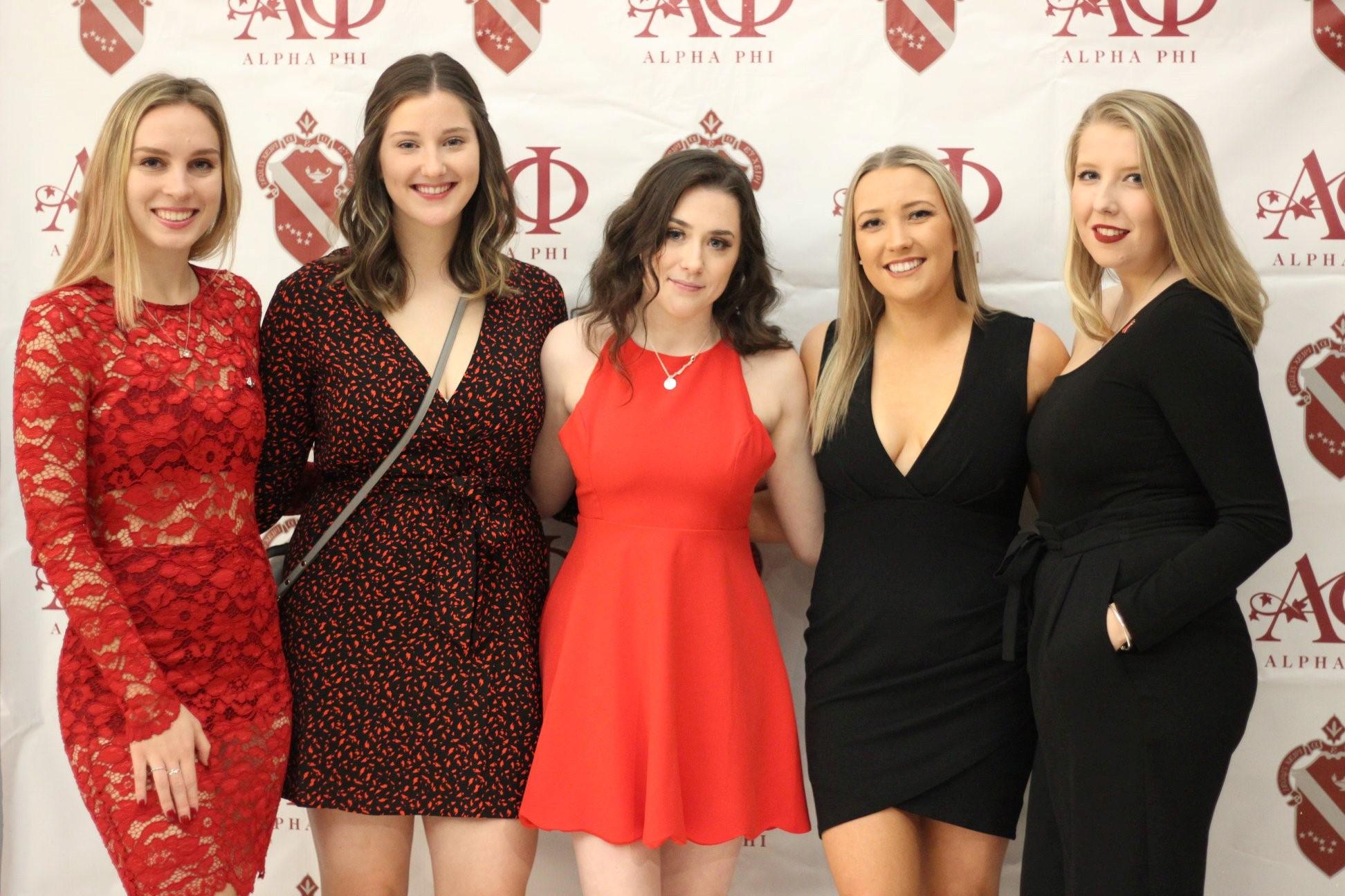 Women in front a greek backdrop.
