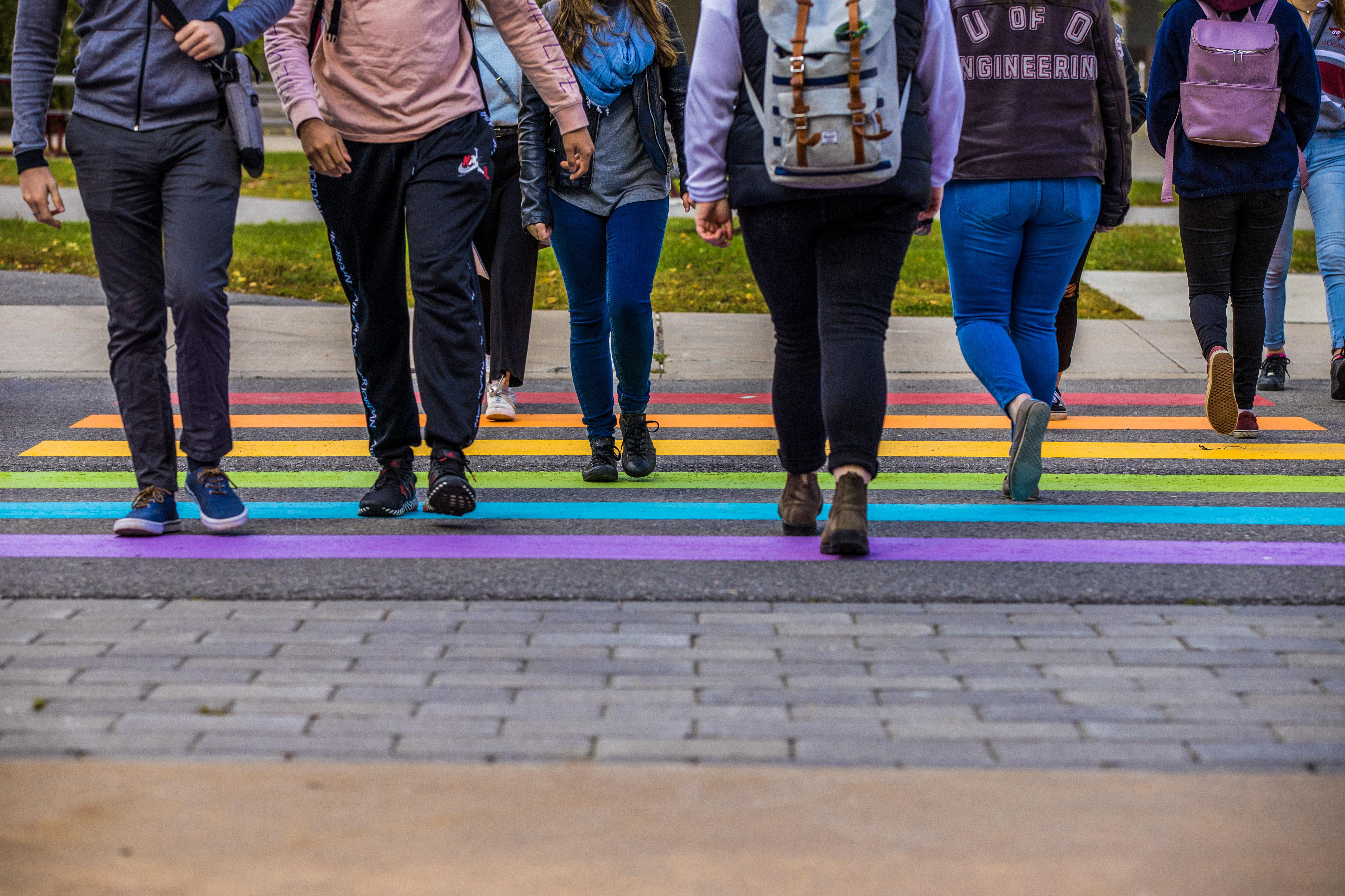 Students walking across a pride theme crosswalk