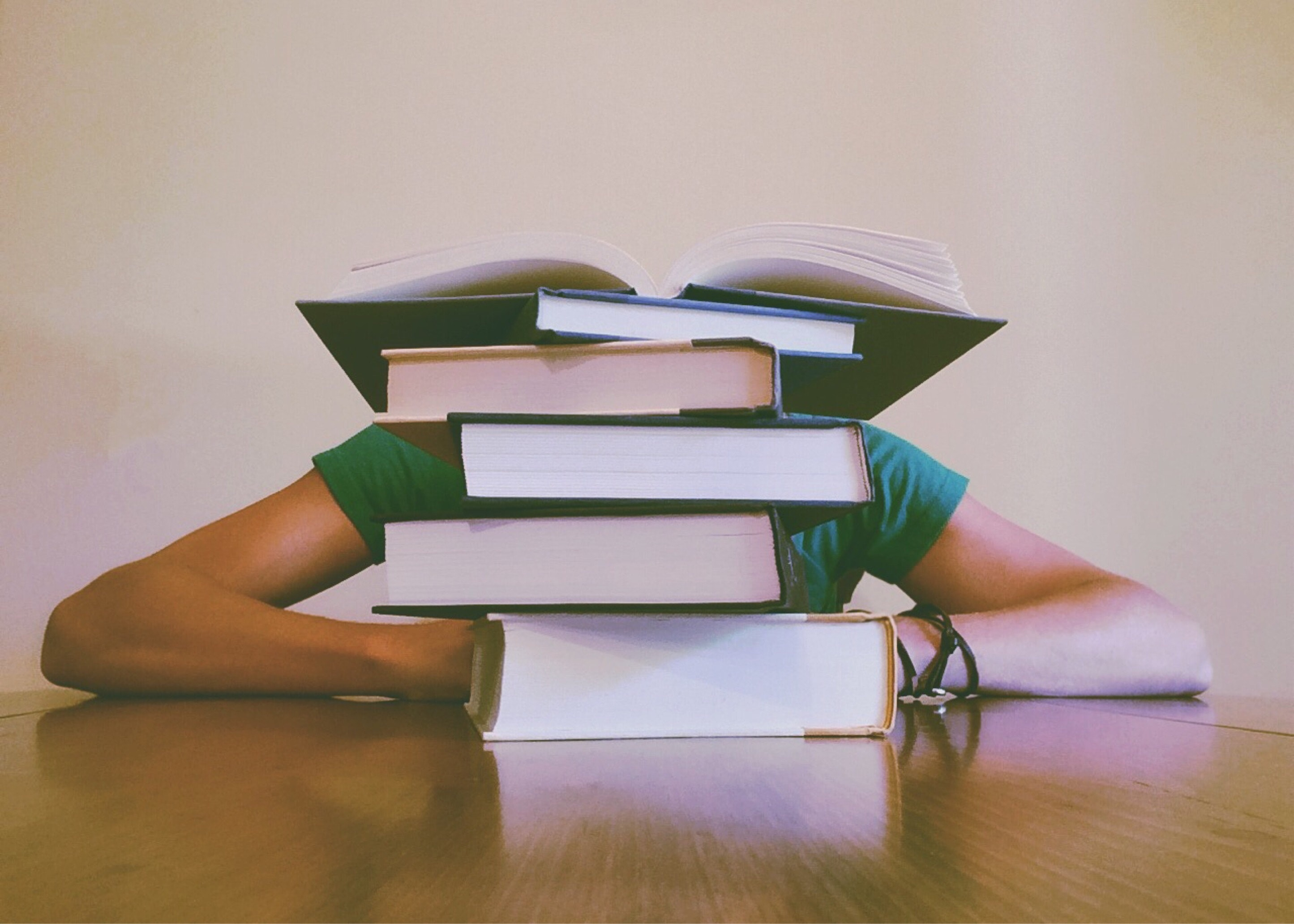 Student sitting behind stack of books