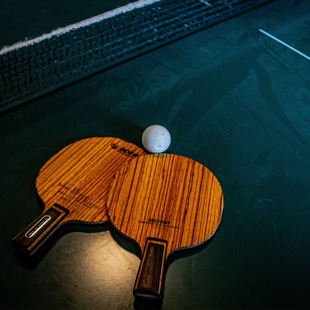Two ping pong rackets and a ball