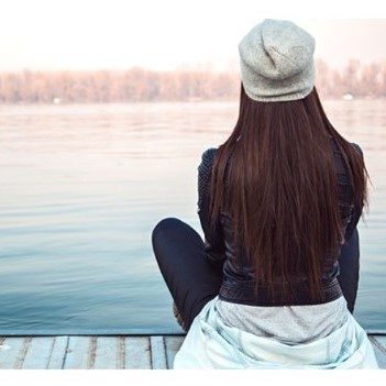 Woman sitting on dock looking out at the water.