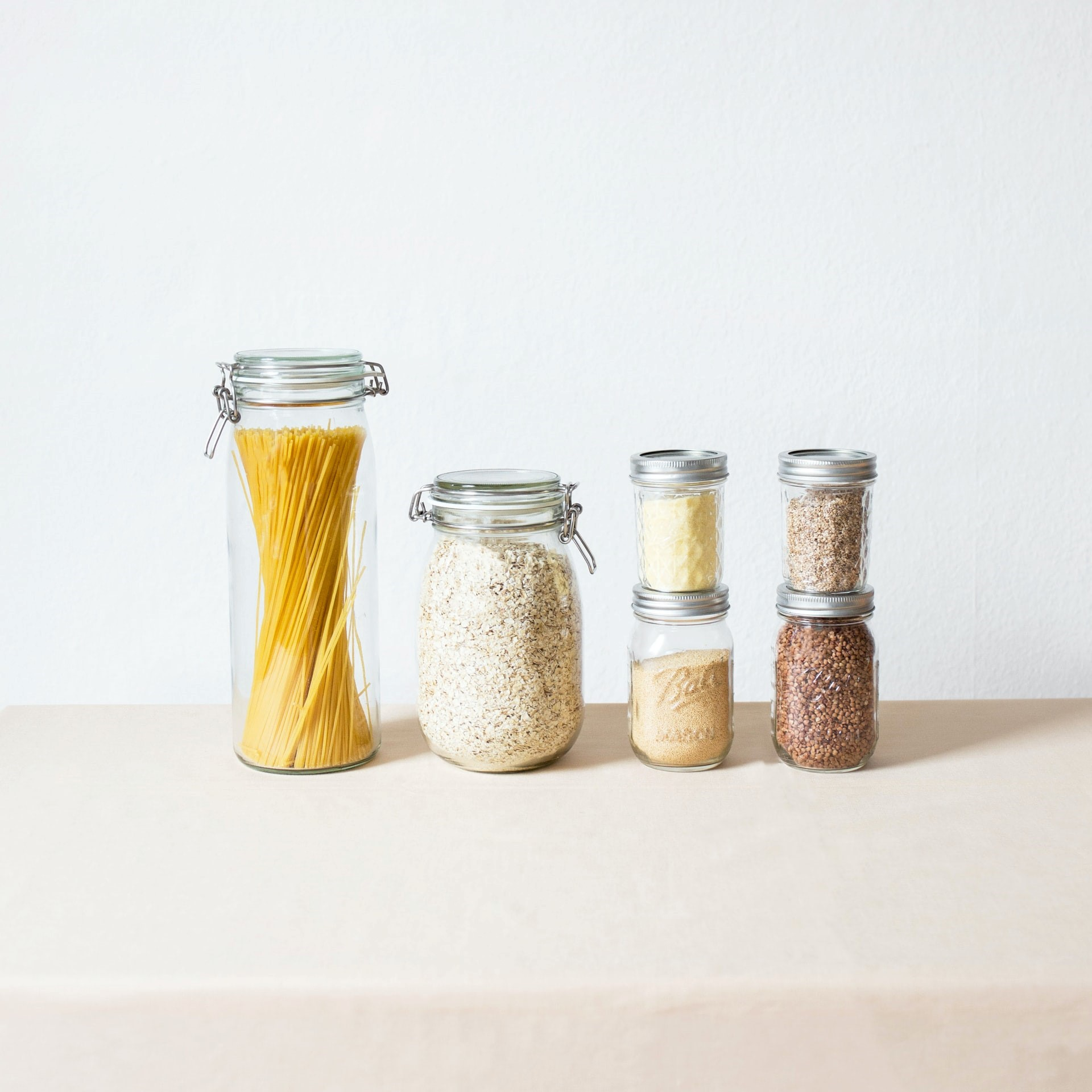 Mason jars filled with pasta, seeds and herbs.