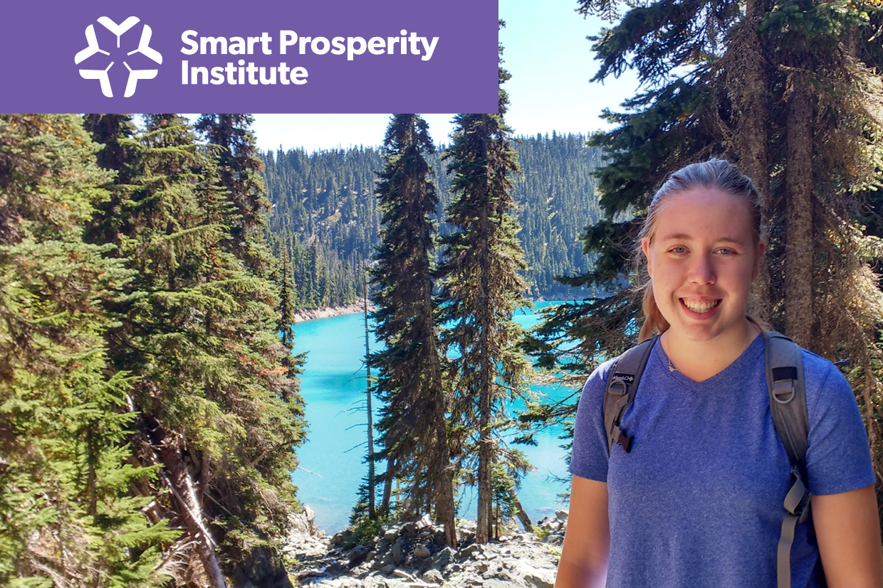 Smiling student poses in front of a beautiful scenery of a blue lake and green pine trees