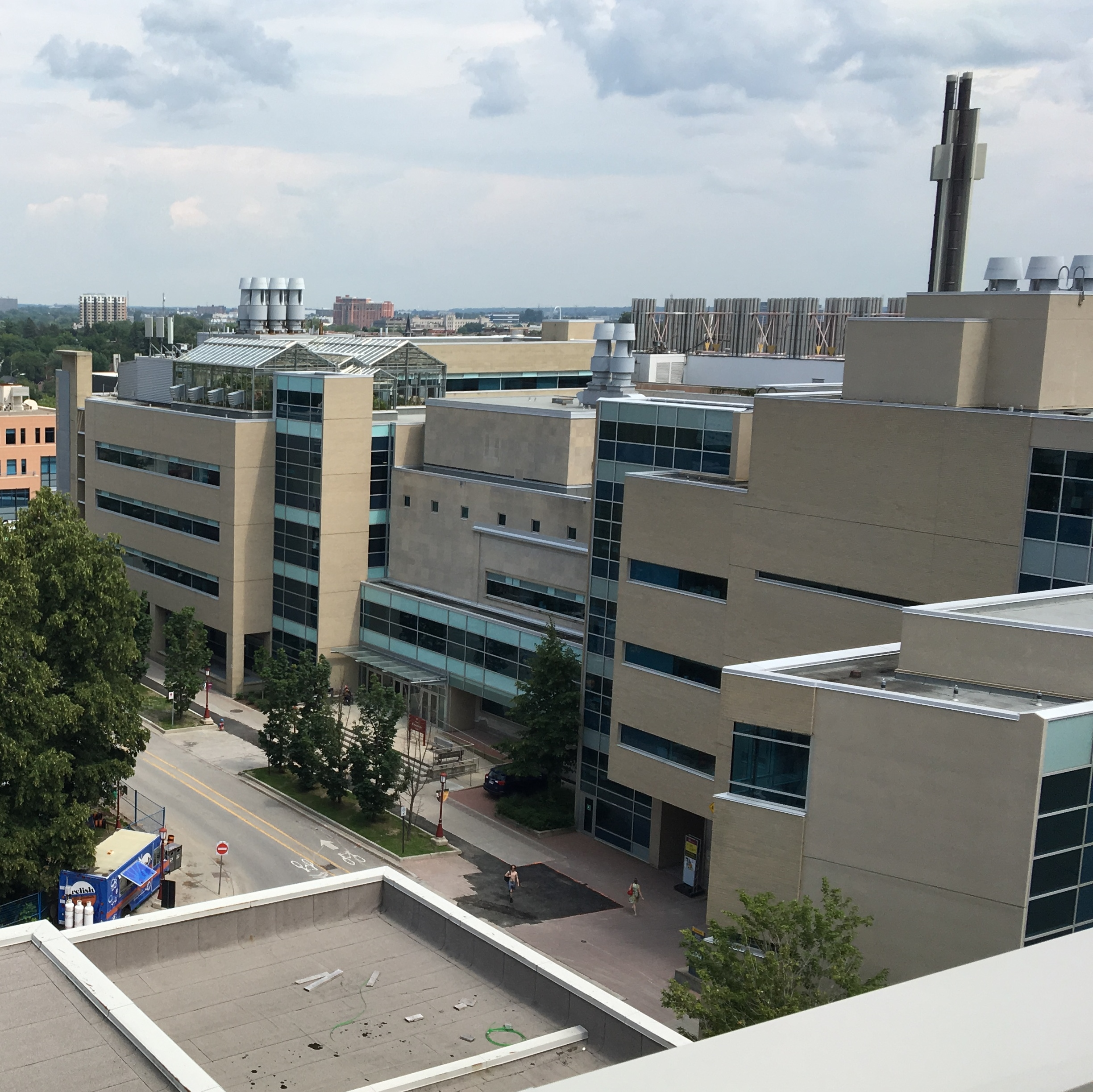 A view of three connected biology buildings as seen from a roof across the street