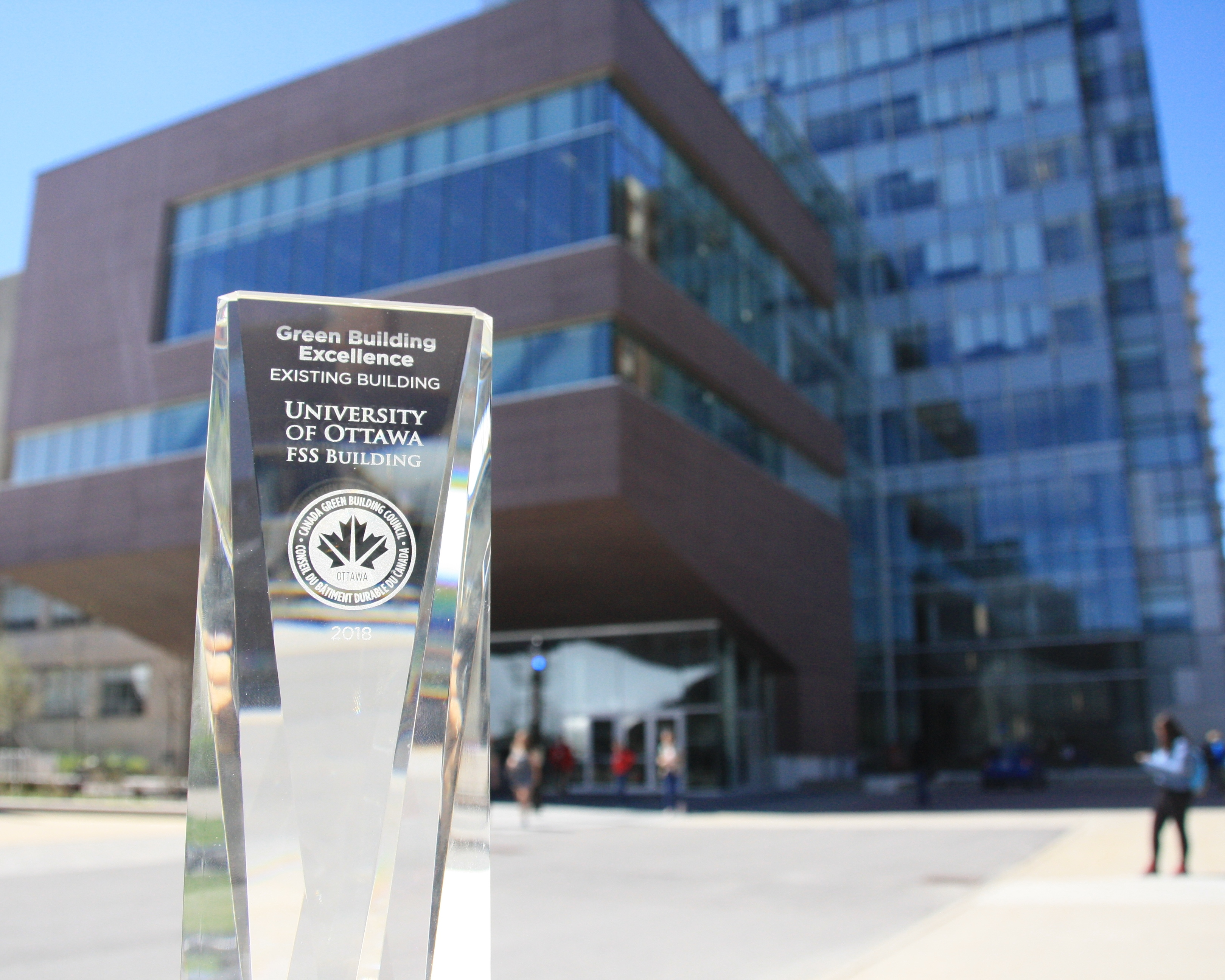 A glass award in front of the Faculty of Social Sciences building.
