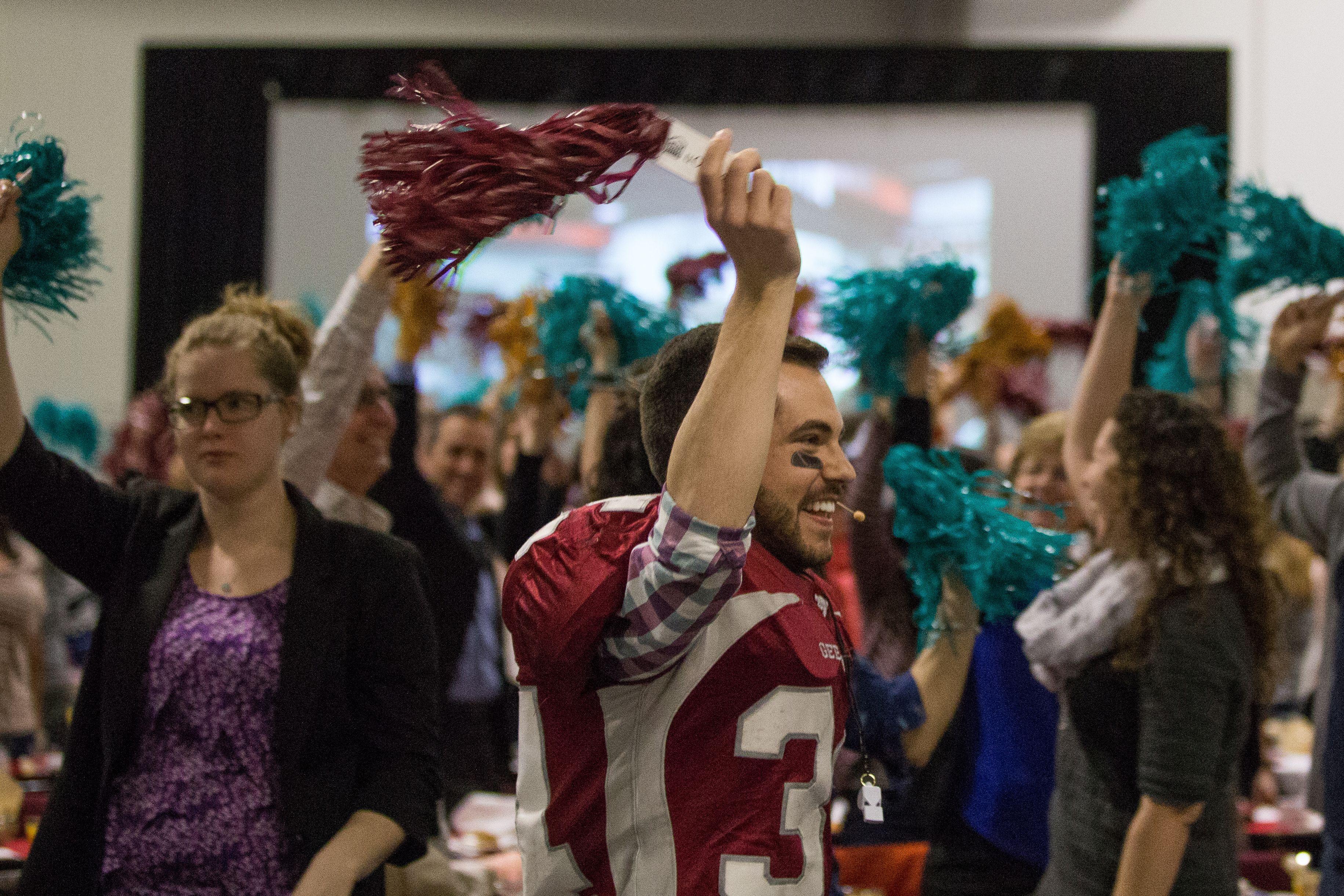 Justin Thibault, à l'avant, revêt un uniforme de footballeur des Gee-Gees et agite un pompon devant une foule; en arrière-plan, le public imite son geste.