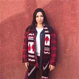 juliana_tpln devant un mur terre cuite qui porte une ceinture fléchée avec des drapeaux canadiens sur ses épaules