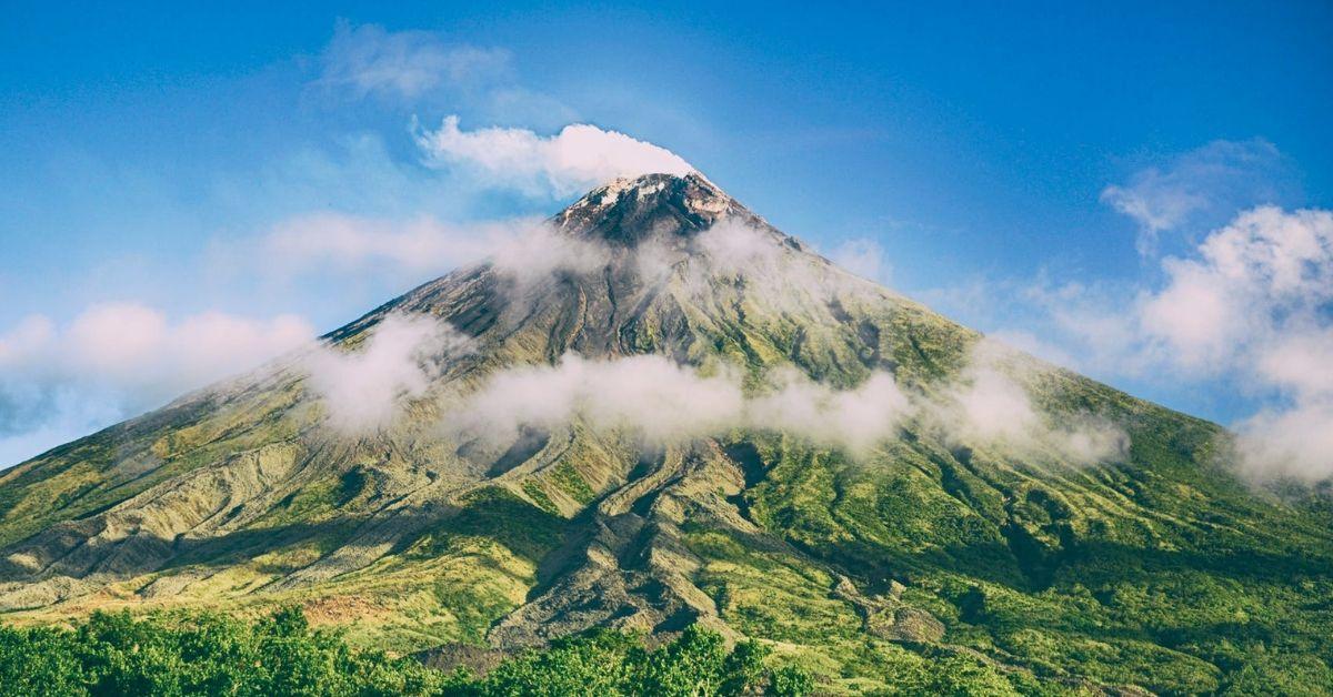 Une montagne couverte de verdure entourée de nuages