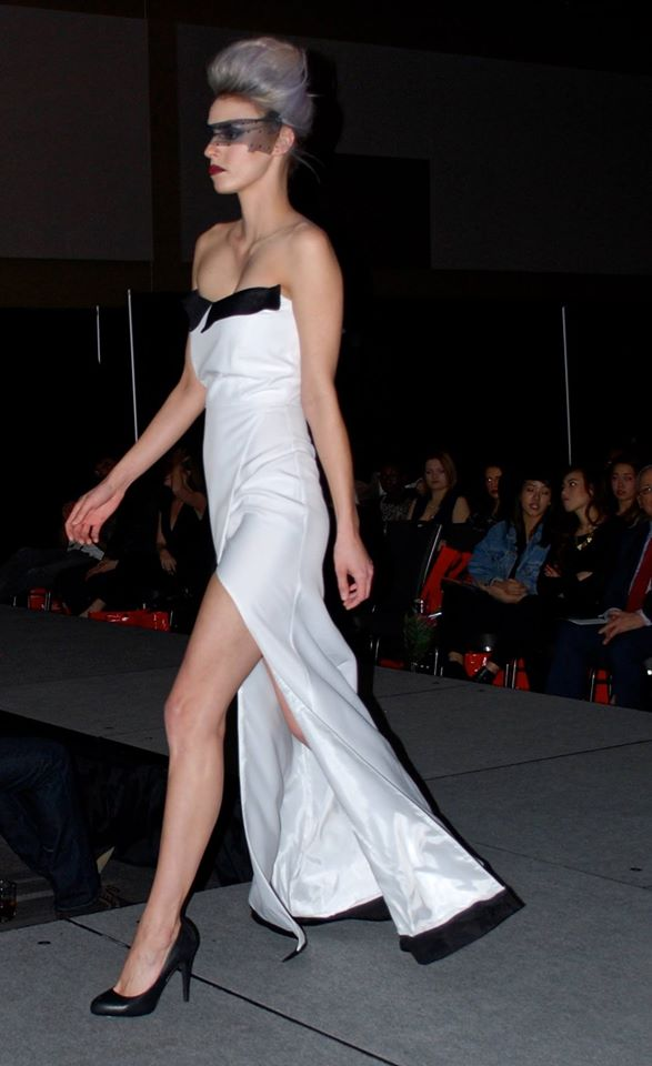 A model in a shimmering white high-slit dress walking down the runway
