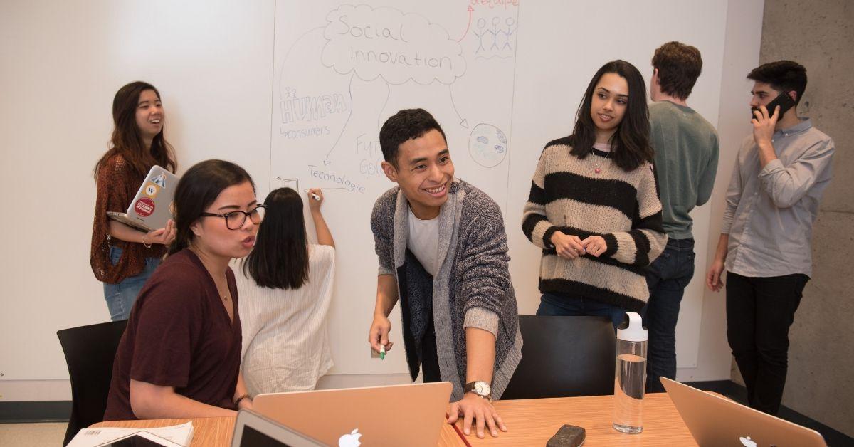 Des étudiants travaillent en classe, certains écrivent sur un tableau blanc.