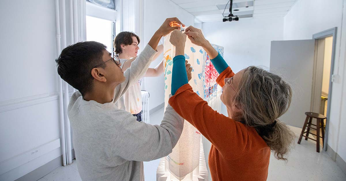 Jennifer Macklem, Willem Deisinger, and Devansh Shah working on their art installation