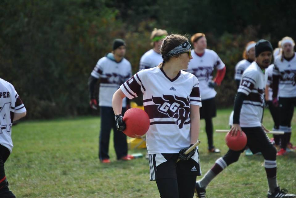 Woman Quidditch player holds a dodgeball under her arm on a field with other players in background