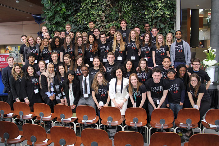 Group of students, including Sara Minaeian, all wearing T-shirts with the words iVote-jeVote.