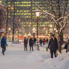 People walking outside on campus during winter, at dusk.