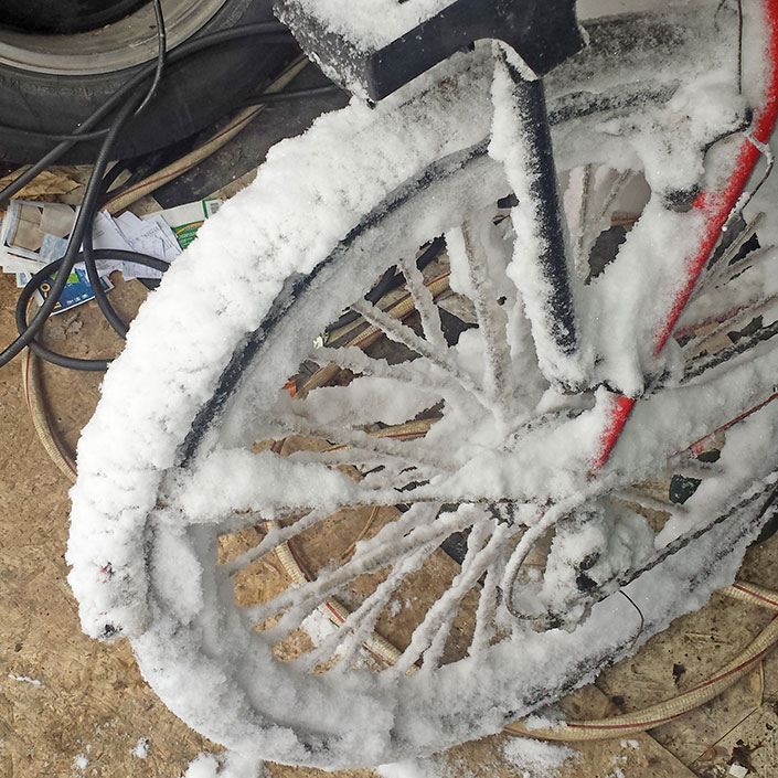 Close-up of a snow-covered bicycle wheel.