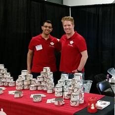 Deux hommes sourient, bras dessus bras dessous, derrière une table de présentation.