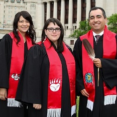 Graduating Indigenous students—two women and a man, who is holding an eagle feather—on the lawn near the Rideau Canal