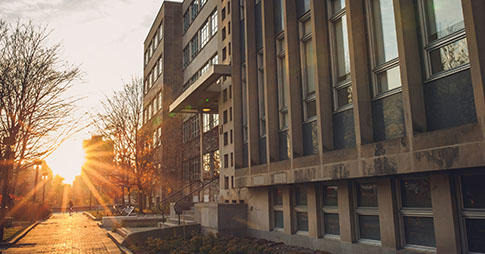 image of sunrise with sun burst with vanier building and walkway