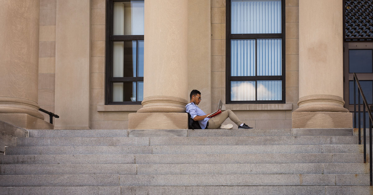 Student with his laptop sitting alone on the steps of Tabaret Hall