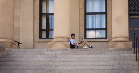 Student with his laptop sitting alone on the steps of Tabaret Hall.
