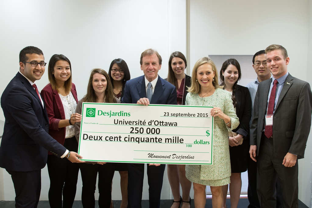 Monique F.Leroux and Allan Rock surrounded by students. Together they hold up a check for 250,000$