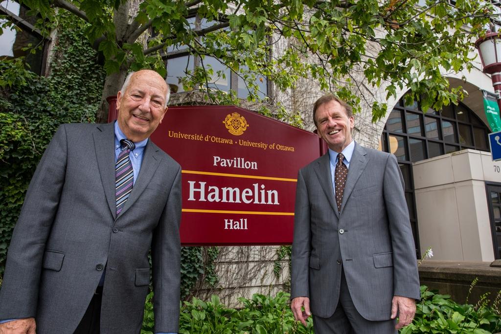 Marcel Hamelin posé devant le panneau du pavillon HAmelin, en compagnie d'Allan Rock, recteur de l'Université d'Ottawa