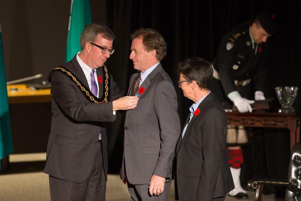 Mayor Jim Watson is attaching the Order of Ottawa pin to Allan Rock's jacket.