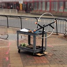 Un appareil fabriqué à partir d'un cerceau et de tuyaux est fixé à un chariot.