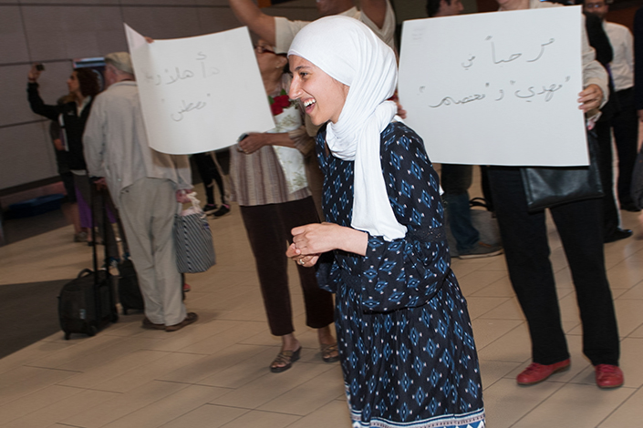Woman smiles. Other people hold signs in Arabic.