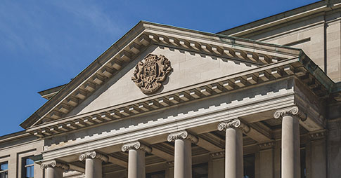 Tabaret hall with university crest on plinth and corinthian columns