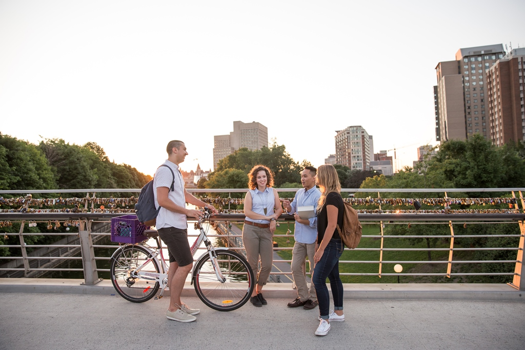 : Four students in conversation stand on the Corktown Bridge that crosses the Rideau Canal and connects uOttawa's with Ottawa's Centretown