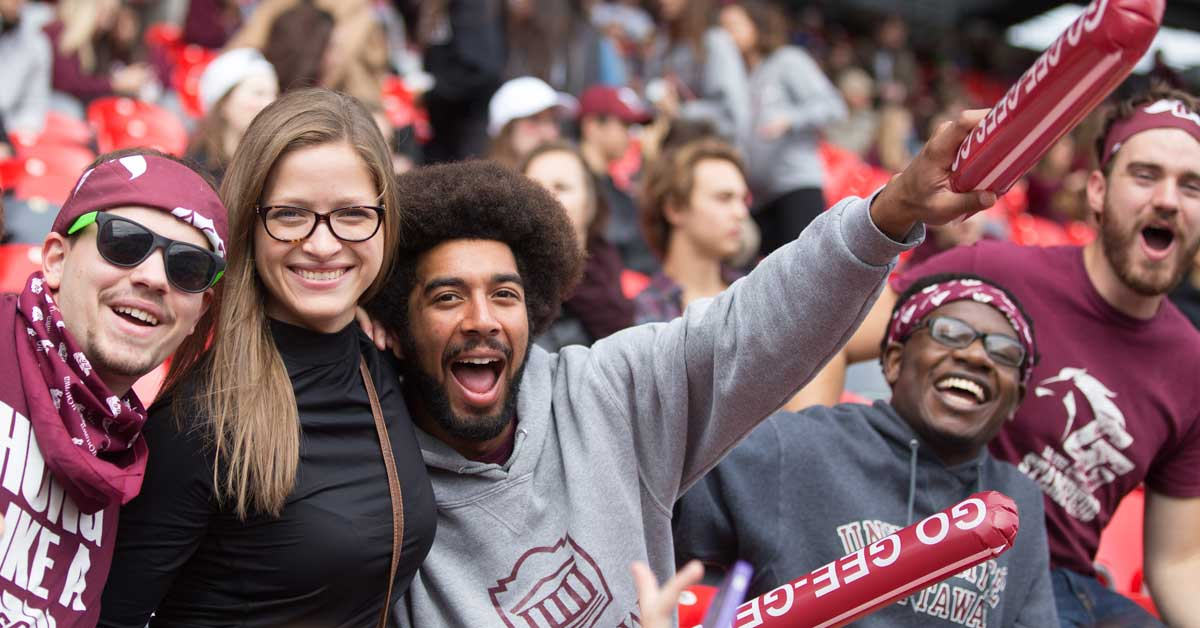 Peter Soroye with an afro cheering on the Gee-Gees at a Panda Game
